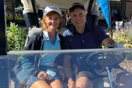 Couple sitting in a golf cart at the Molly Cade Scramble 2020 event